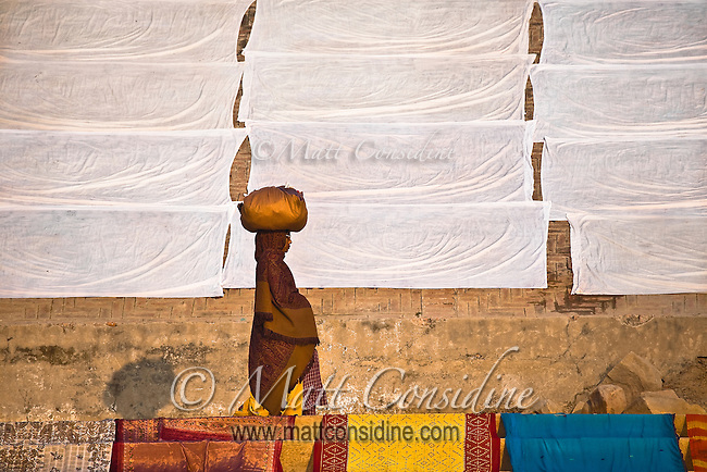 A woman walks past white sheets drying in the sun.<br /> (Photo by Matt Considine - Images of Asia Collection)
