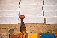 A woman walks past white sheets drying in the sun. (Photo by Matt Considine - Images of Asia Collection)