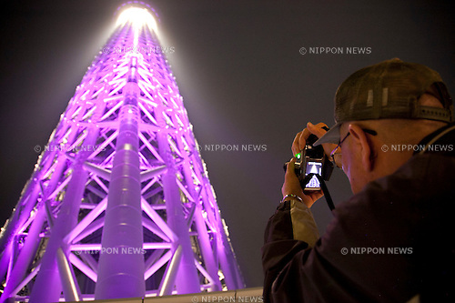 """May 24, 2012, Asakusa, Japan - Visitors take pictures of Tokyo Skytree illuminated in purple which represents the Japanese aesthetic sense, elegant and dignified image of the tower.  ..Tokyo Skytree has two lighting styles, the concept of the design is based on Japanese  aesthetic """"Miyabi"""" in purple and blue """"Iki"""" represents the essence of Kokoroiki. The tower opened to the public on May 22nd 2012 and at 634m is the worlds' 2nd tallest building and the worlds' tallest tower."""