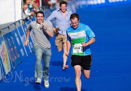 06 AUG 2011 - LONDON,GBR - Relay team members join their runner as he finishes the age group sprint race during triathlon's ITU World Championship Series (PHOTO (C) NIGEL FARROW)