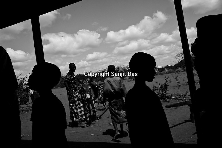 A group of refugees stand under a shade outside a food distribution point in the IFO Camp of the Dadaab refugee camp in northeastern Kenya. Hundreds of thousands of refugees are fleeing lands in Somalia due to severe drought and arriving in what has become the world's largest refugee camp. Photo: Sanjit Das/Panos