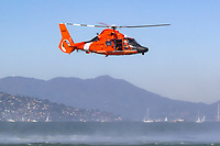 Coast Guard MH-65 Dolphin helicopter from Air Station San Francisco hovers over San Francisco Bay.