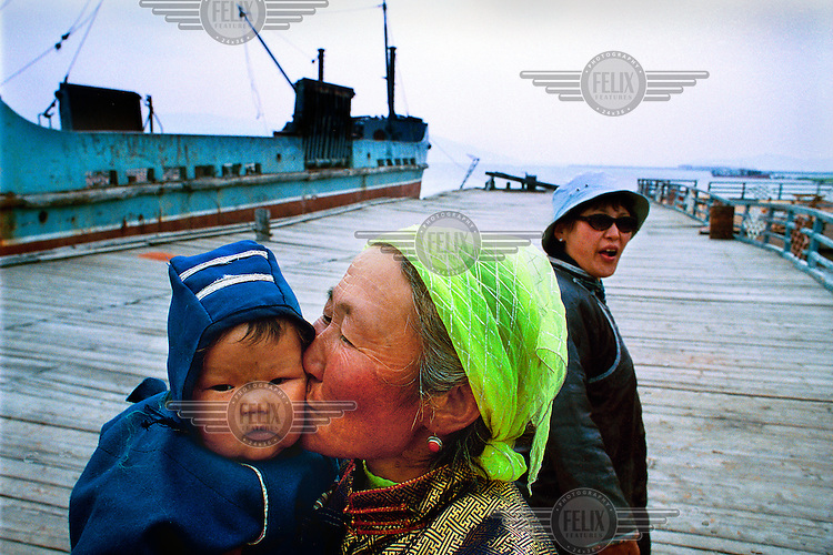 Grandmother and grandchild at the port of Khatgal on Lake Khovsgol. The harbour was once an important link for trade with Siberia, importing oil and exporting uranium. After the fall of the Soviet Union business collapsed and Khatgal became a ghost port.