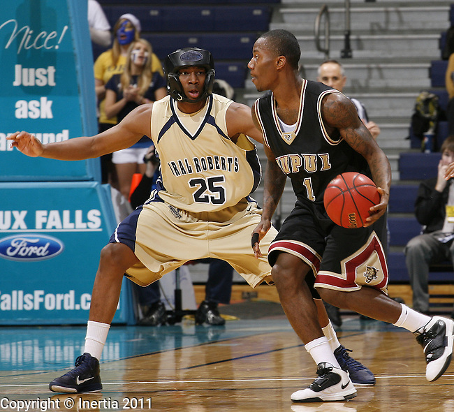 SIOUX FALLS, SD - MARCH 7: Leroy Nobles #1 of IUPUI dribbles toward Oral Roberts defender Kyron Stokes #25 during their semi-final game at the men's 2011 Summit League Basketball Championships in Sioux Falls, S.D. (Photo by Dick Carlson/Inertia)