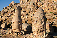 Statue heads, from right, Herekles & Apollo  in front of the stone pyramid 62 BC Royal Tomb of King Antiochus I Theos of Commagene, east Terrace, Mount Nemrut or Nemrud Dagi summit, near Adıyaman, Turkey