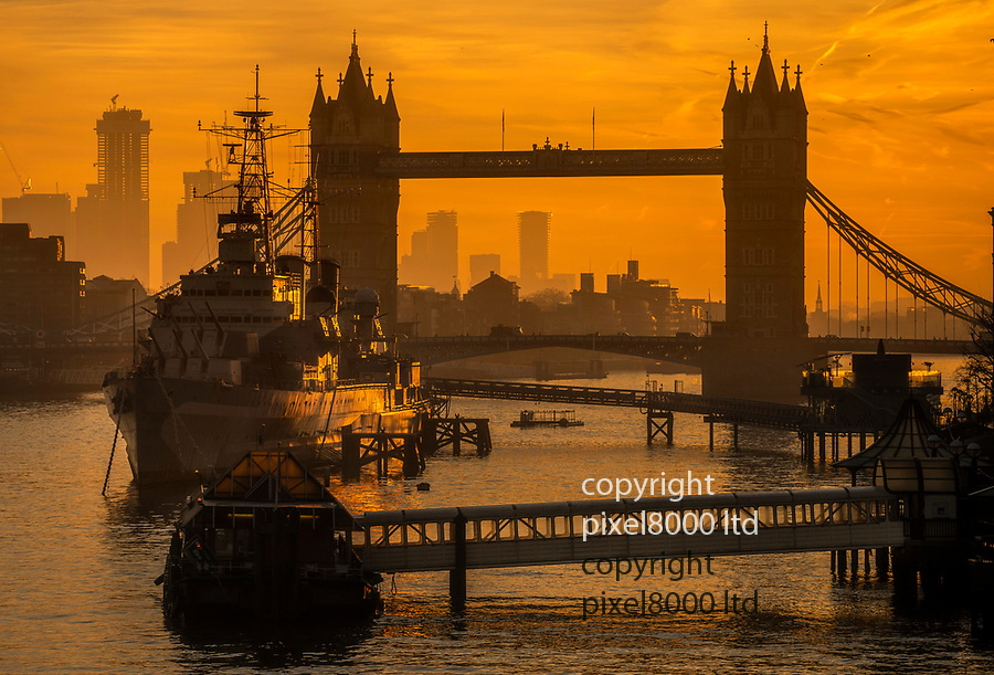 Pic shows: A golden dawn breaks on an unseasonably warm Valentine's Day <br /> to bathe Tower Bridge, and HMS Belfast moored on the Thames in a gorgeous amber light.<br /> <br /> Canary Wharf can be seen in the background<br /> <br /> <br /> <br /> <br /> picture by Andrew Baker/ Pixel8000