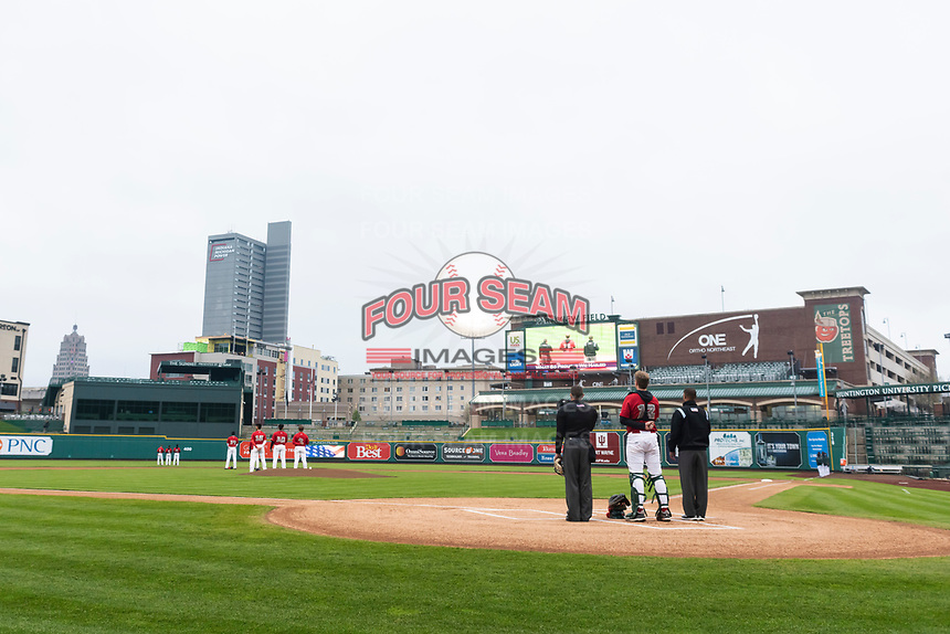 The Fort Wayne TinCaps and umpires stand on the field during the National Anthem before a Midwest League game against the Fort Wayne TinCaps at Parkview Field on April 30, 2019 in Fort Wayne, Indiana. Kane County defeated Fort Wayne 7-4. (Zachary Lucy/Four Seam Images)