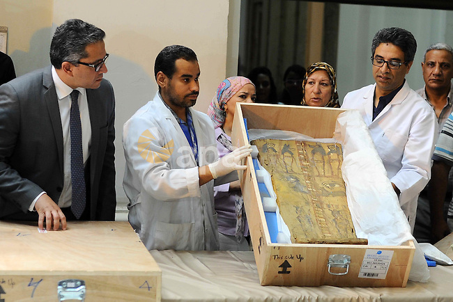 Egyptian antiquities officials inspect a sarcophagus cover on its arrival to the Egyptian Museum in Cairo, Egypt, on June 21, 2016. Two ancient Egyptian sarcophagus covers have been delivered to Cairo's Egyptian Museum after they surfaced at an auction in Israel. Antiquities Minister Khaled el-Anani says the colorful wooden covers, decorated with hieroglyphics and illustrations, were recovered after they went on sale in 2012 and returned following cooperation between the two countries and Interpol. Photo by Amr Sayed