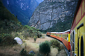 Urubamba Valley, Peru. Local train from Machu Picchu with diesel engine passing through steep area of valley.