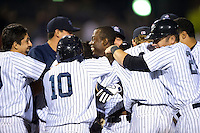 Empire State Yankees outfielder Melky Mesa is mobbed by teammates, including Austin Romine #24, Corban Joseph #1, and Ronnier Mustelier #10, at home after hitting a two run walk off home run during game three of a best of five playoff series against the Pawtucket Red Sox at Frontier Field on September 7, 2012 in Rochester, New York.  Empire State defeated Pawtucket 4-3 to send the series to game four as Pawtucket leads two games to one.  (Mike Janes/Four Seam Images)