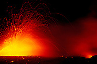 Lava explodes into a fountain of yellow and red in Hawaii Volcanoes National Park.