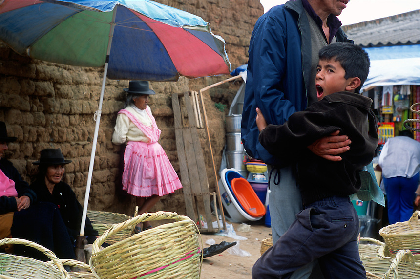 """A boy yawns in his father's arms in the local produce market in Vallegrande, Bolivia Sunday, Nov. 14, 2004. Ernesto """"Che"""" Guevara was captured by the Bolivian army in 1967 in a nearby valley and executed in La Higuera days later. His body was put on public display in the laundry room of the Vallegrande hospital, then secretly buried under the air strip for 30 years. Guevara and fellow communist guerillas were attempting to launch a continent-wide revolution modeled on Guevara's success in Cuba in the late 1950s. The Bolivian government recently began promoting the area where he fought, was captured, killed and burried for 30 years as the """"Ruta del Che,"""" or Che's Route. (Kevin Moloney for the New York Times)"""