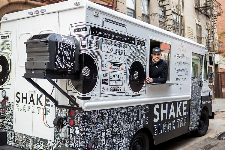 Chef Joe Isidori in one of two renovated vintage Black Tap trucks, in front of a garage in Harlem, that will be roving the city streets this summer serving milkshakes. A third truck is in progress with plans to be stationed in the Hamptons.<br /> <br /> Danny Ghitis for The New York Times