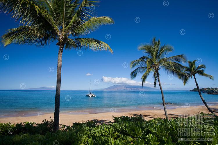 Sailboat heads out at Makena Beach, Maui, Hawaii.