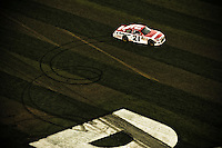 """Winner Trevor Bayne (#21) cuts some doughnut through the infield grass in the spape a an """"E"""" on the 10th anniversity of Dale Earnhardt's final Daytona 500."""