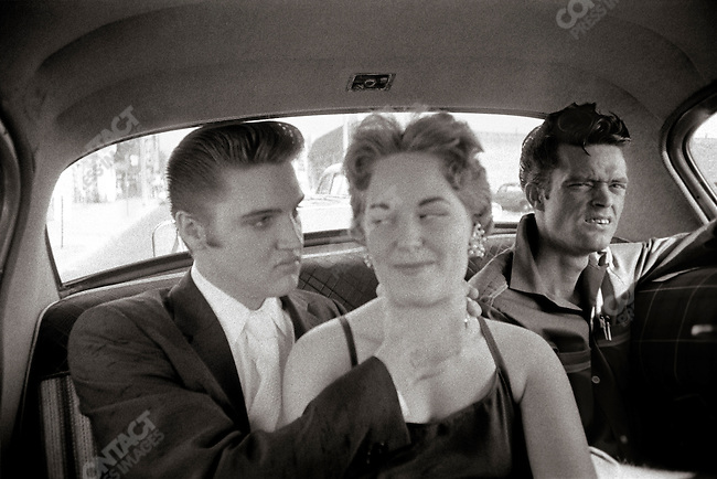 Elvis taking a girl that he had met earlier at a luncheonette to the Mosque Theater. A bit later, she is going to become the girl of the kiss. On the right, Elvis friend's Junior Smith. Richmond, Virginia, USA, June 30, 1956
