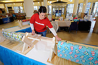 NWA Media/ J.T. Wampler - Jody Bergstrom wraps Christmas presents Monday Dec. 22, 2014 at the food pavilion at Pinnacle Hills Promenade. Presents will be wrapped for until Christmas Eve at 3p.m. Donations are accepted for the wrapping service with proceeds benefitting the Camp Alliance Silver Star Gift Program.