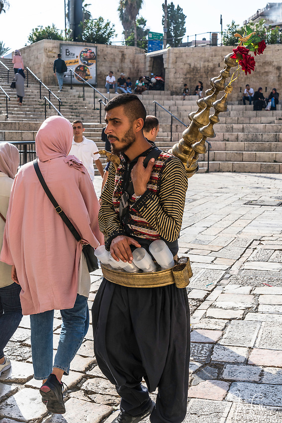 A Palestinian Arab man with his copper teapot on his back sells a cold drink made of tamarind juice and rose water by the Damascus Gate in East Jerusalem.