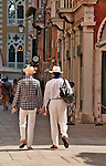 Two men walk down a street in Venice, Italy during the summer