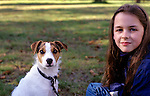 Young girl sitting with her puppy ( Jack Russell Terrier) smiling at camera