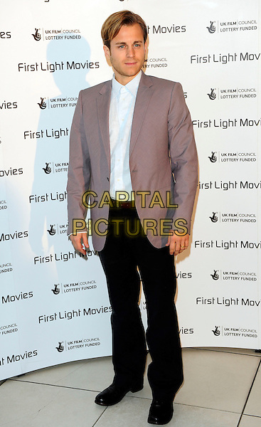 KEVIN BISHOP .Inside Arrivals - The First Light Film Awards 2010, Odeon Leicester Square, .London, England, UK,.2nd March 2010..full length suit jacket black trousers  white shirt grey gray .CAP/CJ.©Chris Joseph/Capital Pictures.