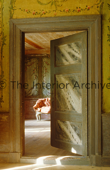 This door in a wall hand-painted with garlands opens into a room with painted frescoes