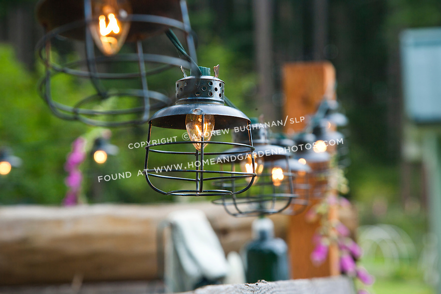 A string of lights illuminates a rustic outdoor shower in the Pacific Northwest.