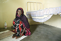 Djibouti. Tadjourah province. Tadjourah. Centre médico hospitalier (CMH). Hospital. An old black muslim woman, wearing a veil on her head, sits on the ground below her bed. She is suffering from HIV Aids and tuberculosis. The Global Fund through the djiboutian Ministry of Health supports the hospital with an Aids grant (financial aid).  © 2006 Didier Ruef