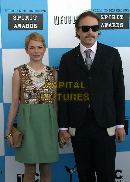 MICHELLE WILLIAMS & HEATH LEDGER.2007 Film Independent's Spirit Awards at the Santa Monica Pier, Santa Monica, California, USA,.24 February 2007..half length green skirt gold beaded dress beige brown holding hands black suit .CAP/ADM/BP.©Byron Purvis/AdMedia/Capital Pictures.