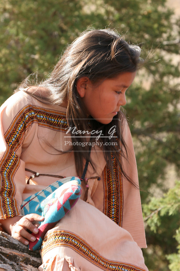 A young Native American Indian girl sitting in a tree playing