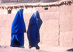 Two Afghan refugee women walk through the Shamshatoo refugee camp dressed in burkas..