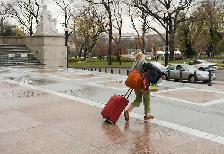 Emily Roth from the office of Rep. Lacy Clay, D-Mo., leaves Rayburn Building for Thanksgiving break, en route to Rhode Island, Nov. 24, 2009.
