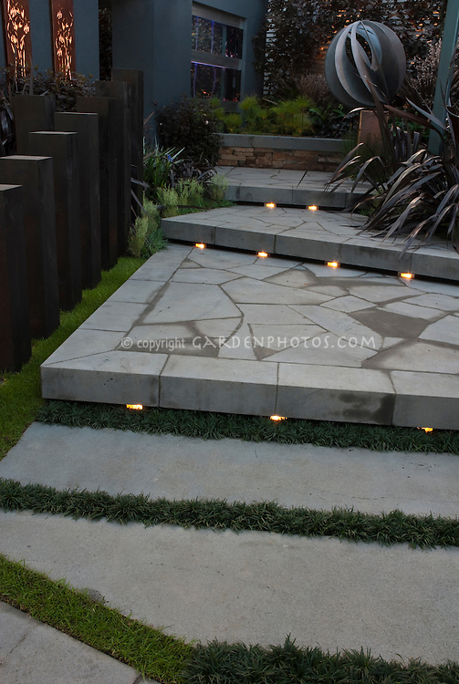 Beautiful blue tones patio steps with built-in lighting, birch trees, landscaping, arbor, garden ornament in evening