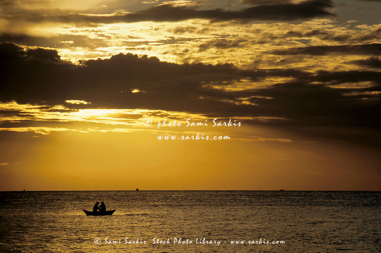 Fishermen in a rowboat silhouetted at sunrise.