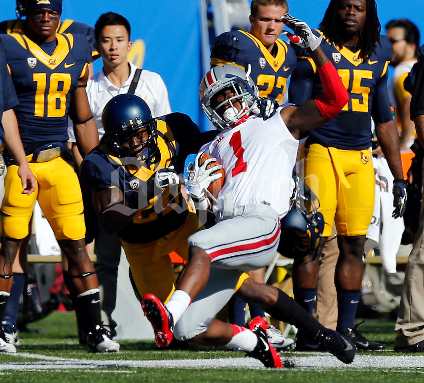 Ohio State Buckeyes running back Dontre Wilson (1) is tackled out of bounds by California Golden Bears defensive back Isaac Lapite (20) during the first quarter of the NCAA football game at Memorial Stadium in Berkeley, California on Sept. 14, 2013. (Adam Cairns / The Columbus Dispatch)