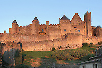 Citadel of Carcassonne at twilight, 13th century, Carcassonne, Aude, France. The two outer walls of the concentric fortified city are defended by towers and barbicans, and a draw bridge across a moat leads to the keep of the castle. Carcassonne was a stronghold of Occitan Cathars during the Albigensian Crusades but was captured by Simon de Montfort in 1209. He added extra fortifications and Carcassonne became a citadel on the French border with Aragon. The fortress was restored in 1853 by Eugene Viollet-le-Duc. Today it is a UNESCO World Heritage site. Picture by Manuel Cohen.