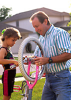 A loving father helps his little girl fix her bike in yard at home