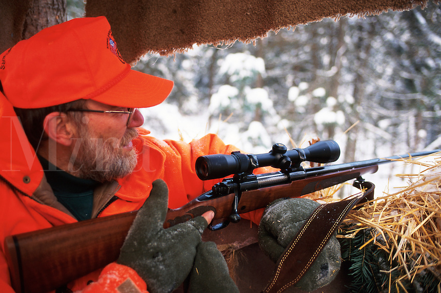 A deer hunter in orange safety hunting gear holding a rifle within a winter hunting blind.