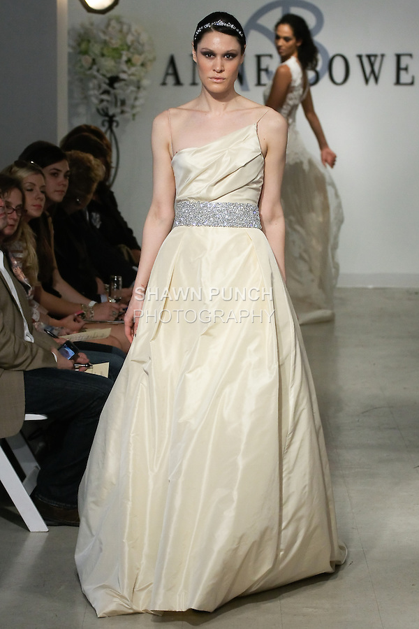 """Model walks runway in a Charity Bridal gown - champange silk taffeta ball gown with crystal and satin faced organza belt, from the Anne Bowen Bridal Spring 2013 """"Coat of Arms"""" collection fashion show, during Bridal Fashion Week New York April 2012."""