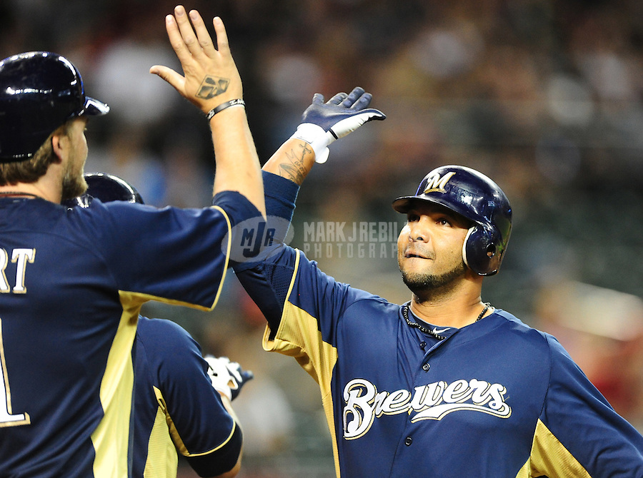 Apr. 3, 2012; Phoenix, AZ, USA; Milwaukee Brewers shortstop Alex Gonzalez (right) is congratulated by teammates after hitting a two run home run in the fourth inning against the Arizona Diamondbacks during a spring training game at Chase Field.  Mandatory Credit: Mark J. Rebilas-