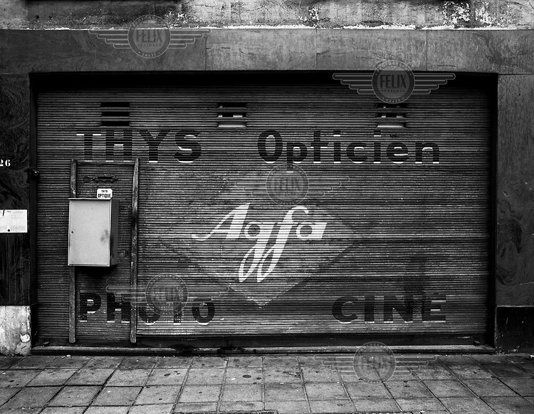 A shuttered shop selling photographic goods.