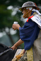 Participant enjoys a beer after a horse race, Somanomaoi Festival, Minami-soma City, Fukushima Prefecture, Japan, July 27, 2013. During the four-day-long Somanomaoi Festival members of old samurai families ride horseback through the town in traditional armour.  They also take conduct ceremonies at local shrines, take part in horse races, and compete on horseback to catch a flag launched into the air by fireworks.