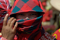Tibetan Nomad Girl covering her face due to the intense sunlight in Tibet