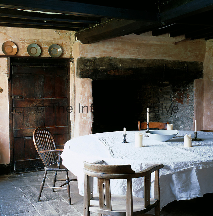 A circular table made from a piece of plywood is placed on wooden blocks in a 16th century room with stone floors, bare plaster walls and a walk-in fireplace