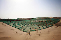 Fortifications aimed at preventing the movement of sand dunes in Hebei Province, China.. Desertification is the process by which fertile land becomes desert, typically as a result of drought, deforestation, or inappropriate agriculture. 41 % of China's landmass in classified as arid or desert. Inappropriate farming methods and over cultivation have contributed to the spreading of deserts in China in recent years.