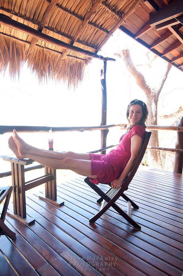 Young woman in red dress relaxing on bamboo thatch shaded bungalow porch, Morgan's Rock Hacienda and Eco Lodge, Nicaragua