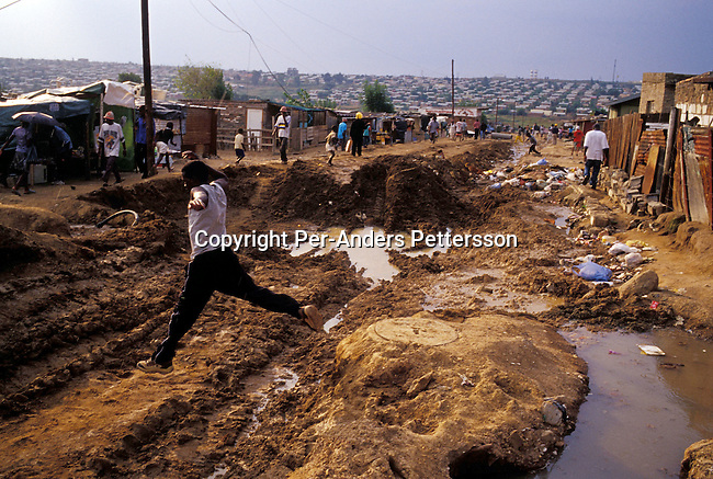 DIEPSLOOT, SOUTH AFRICA - FEBRUARY 29: An unidentified man jumps over a muddy road construction on February 29, 2004 in Diepsloot a township outside Johannesburg, South Africa. Diepsloot is the fastest growing township around Johannesburg as rural South Africans come to Johannesburg to look for work. They face difficulties finding work and housing. Many illegal immigrants from other African countries live in Diepsloot and some of the residents complain that corrupt officials give foreigners with money houses quickly. South Africa faces a backlog of 6-7 million houses and they have built around 1,7 million houses since coming to power in 1994. .(Photo: Per-Anders Pettersson/Getty Images).........