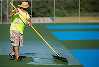 NWA Democrat-Gazette/JASON IVESTER <br /> Jaime Ocampo (cq) with McConnell &amp; Associates speads paint on Thursday, Aug. 13, 2015, across the tennis courts at Rogers High School. The crew have been working on the renovation for two weeks.