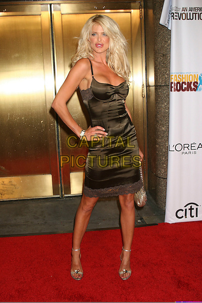 VICTORIA SILVSTEDT.Arrivals at Fashion Rocks held at Radio City Music Hall,.New York, 8th September 2005.full length brown satin metallic shiney dress cleavage hand hip.Ref: IW.www.capitalpictures.com.sales@capitalpictures.com.©Capital Pictures