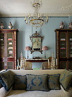 The sitting room is decorated in a cool blue with traditional furnishings in a pleasing symmetry. Large ceramic jars sit atop the tall bookcases and two cane-backed chairs stand either side of a marble-topped Georgian console table.
